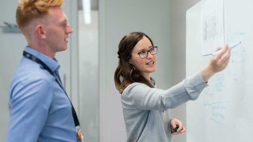 Arbeidskollegaer, mann og kvinne, foran whiteboard