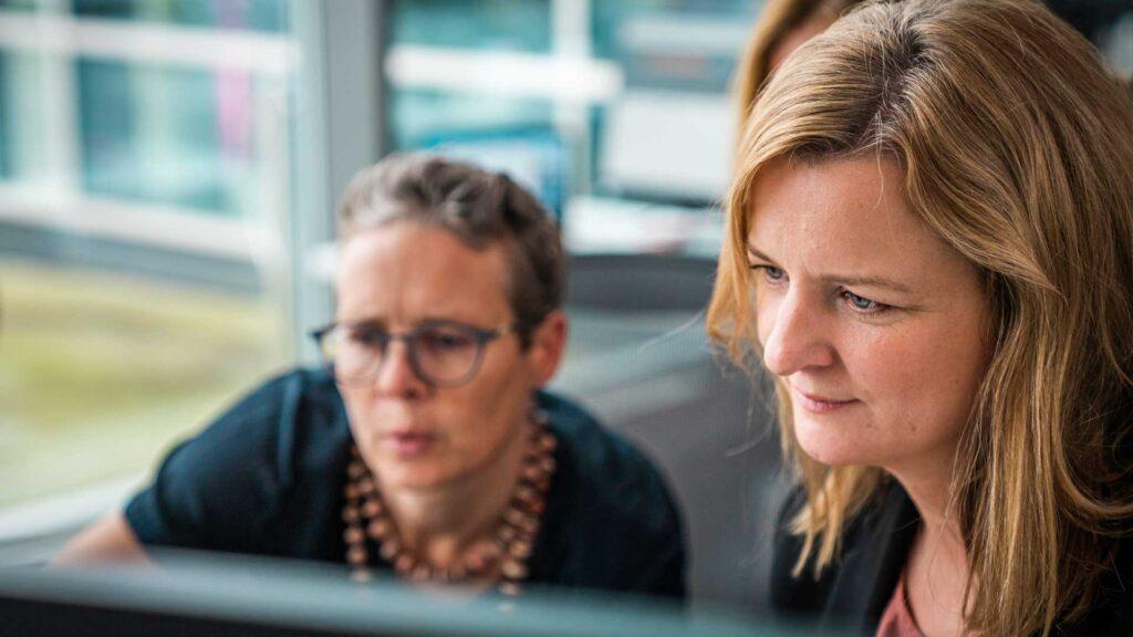 Arbeidskollegaer, to kvinne, foran pc skjerm